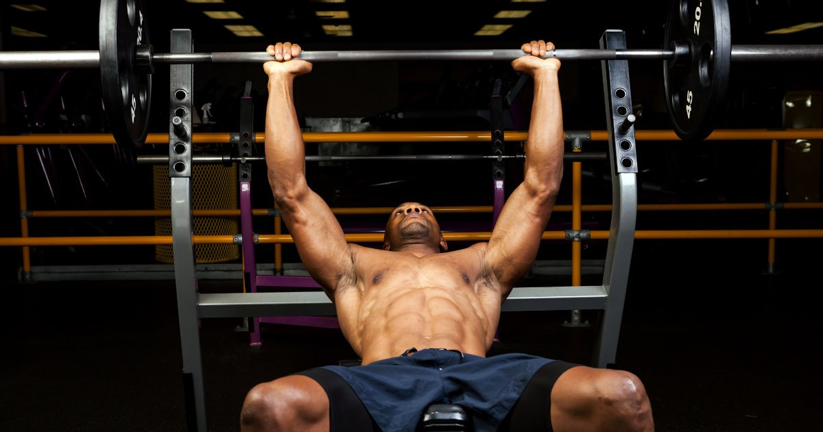 Muscular man doing barbell chest presses