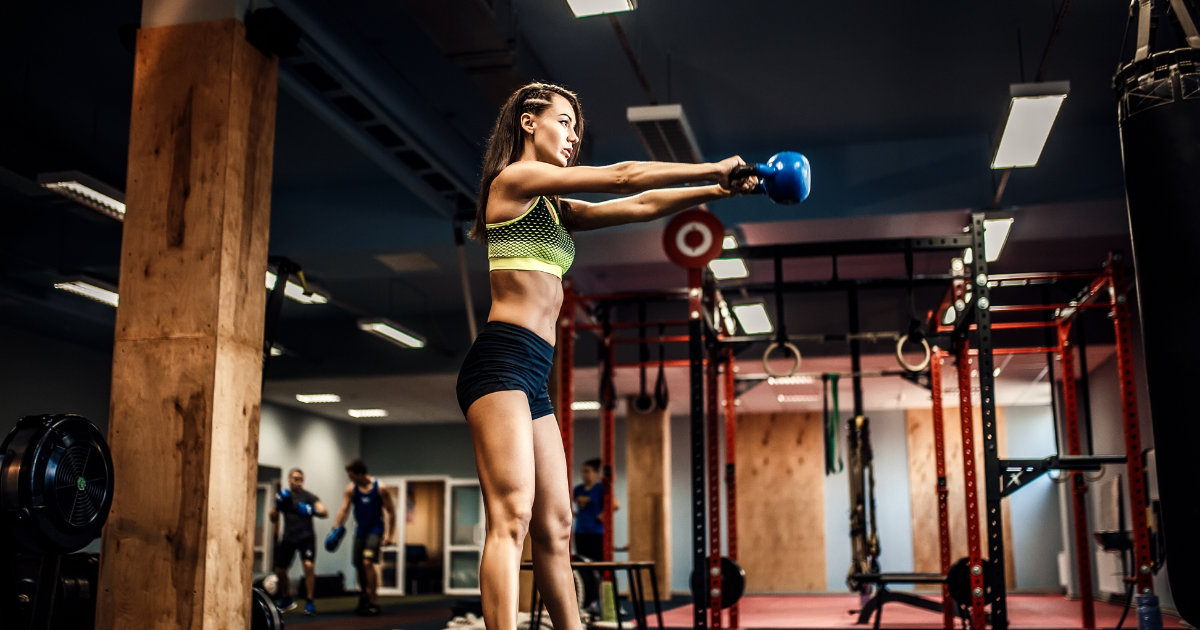 Attractive young female bodybuilder performing kettlebell swings in gym.