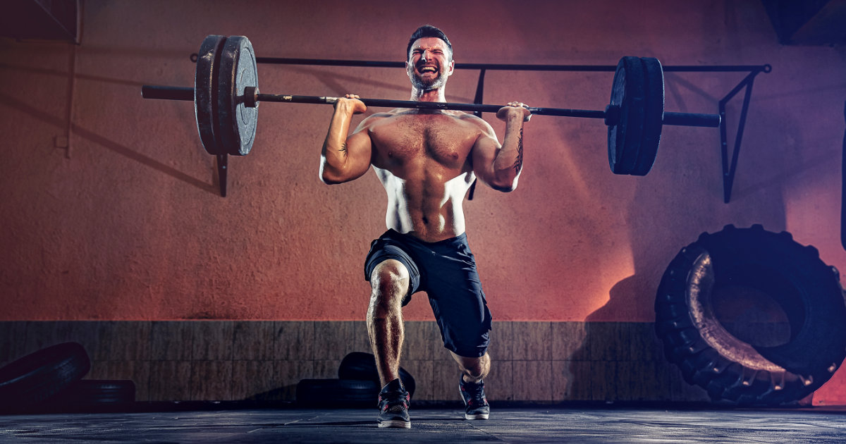 Shirtless, muscular man doing front rack barbell reverse lunges.