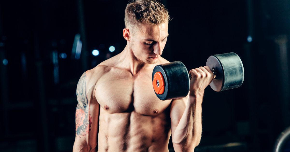 Shirtless muscular man doing single arm bicep curls.