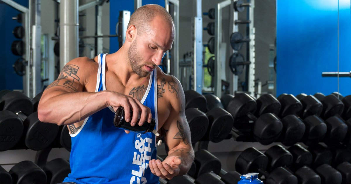 Fit man taking his vitamins in a gym