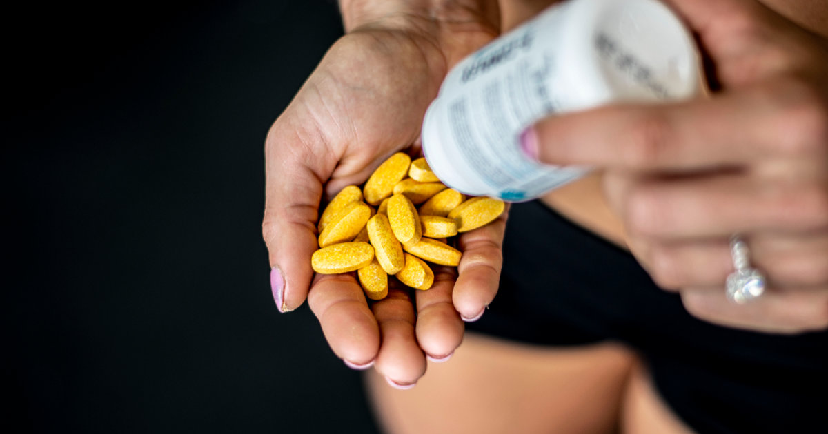Swolverine athlete pouring yellow vitamins into hand.