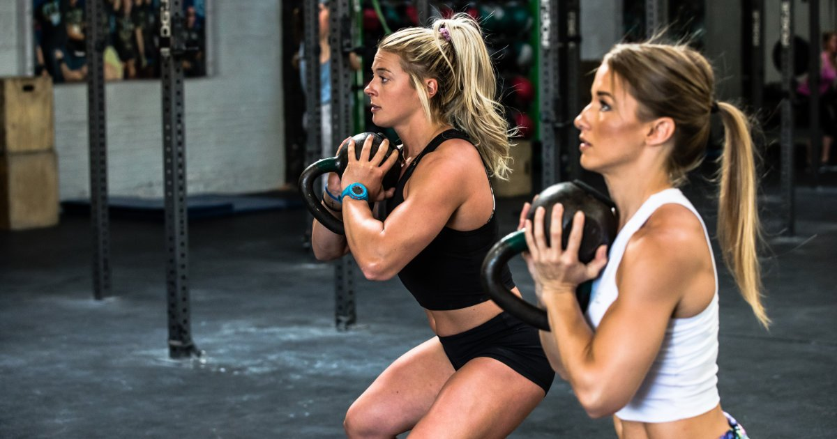 Swolverine athletes doing kettlebell goblet squats in CrossFit-style gym.