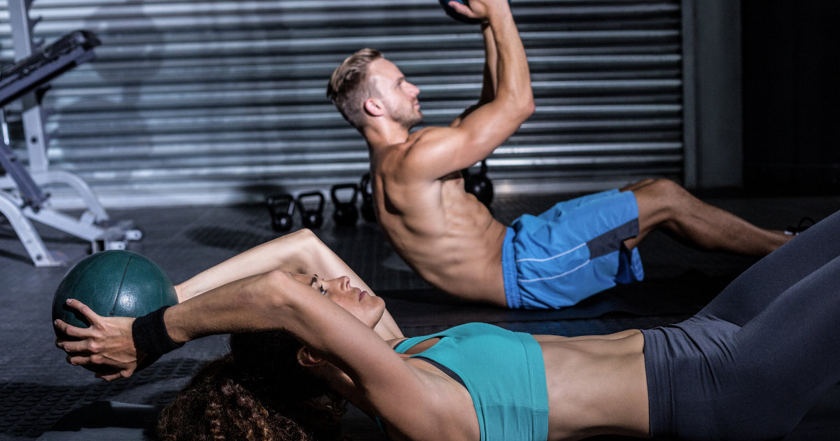 Man and woman doing ab workouts in gym.