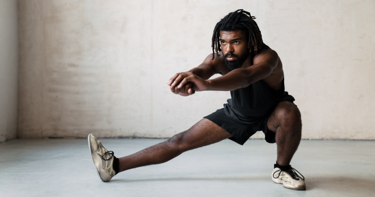 Man in black shorts and black tank top doing lateral lunges.