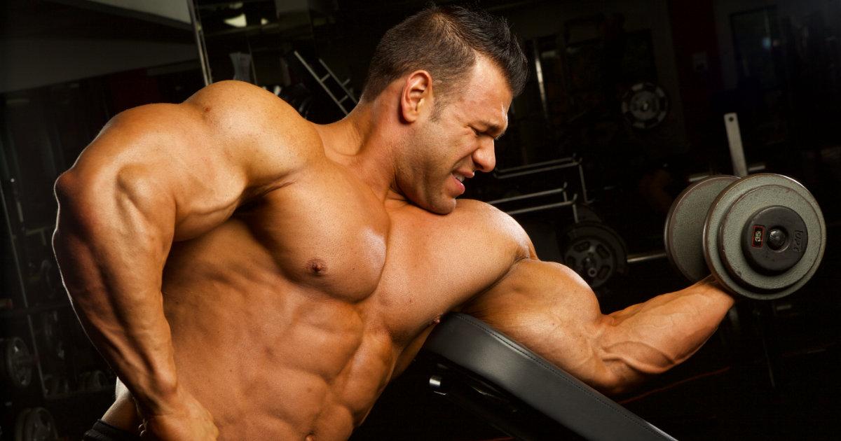 Shirtless muscular man dong single arm bicep curls.