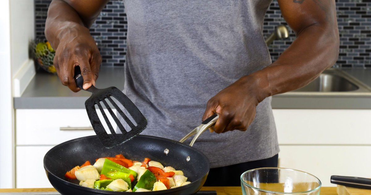 Muscle & Strength athlete in grey M&S t-shit cooking chicken and peppers on the stove.