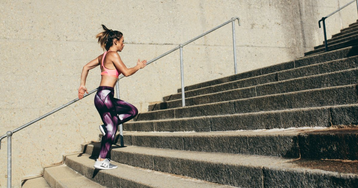 Woman running up stairs outside for cardio.