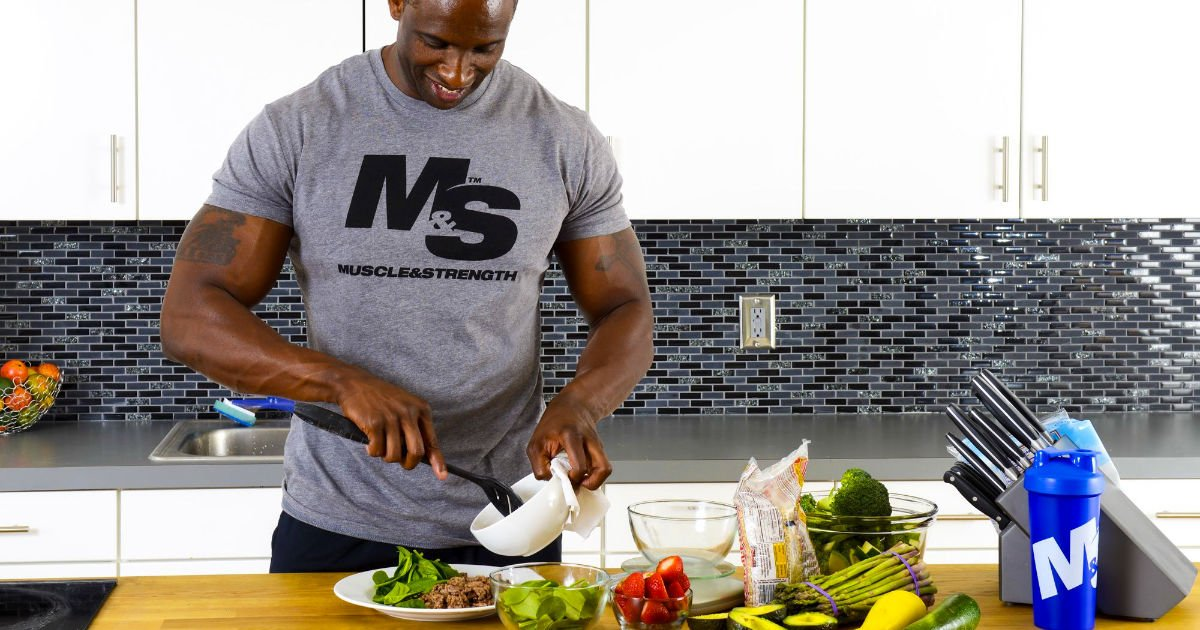 Muscular man in Muscle & Strength t-shirt plating up food.