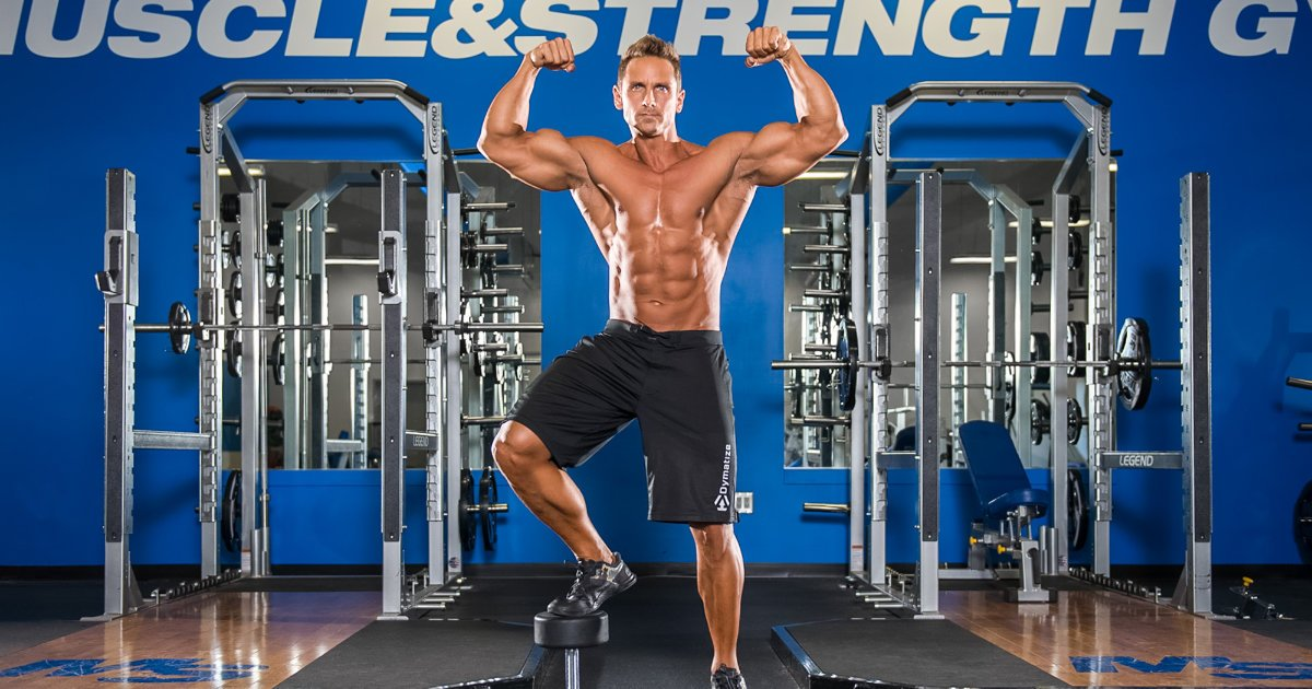 Muscular man flexing his biceps and posing in gym.