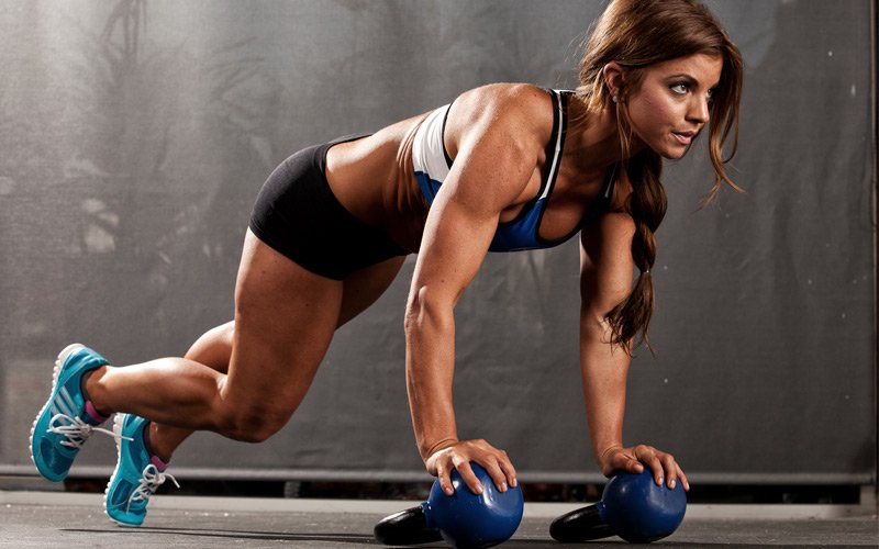 Fit woman doing push up workout on kettlebells