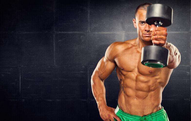Fit muscular man working out with dumbbells