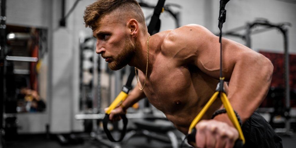 Shirtless muscular man doing TRX pushups.