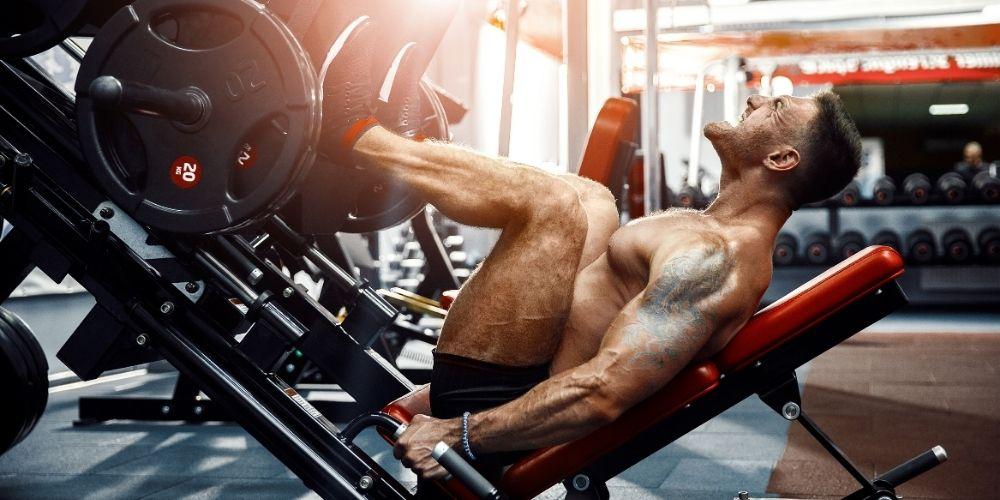 Muscular, shirtless man doing leg press.