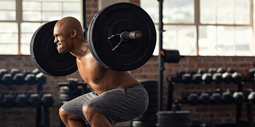 Man in grey shorts performing barbell back squat