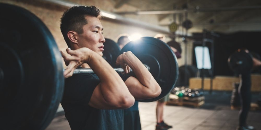 Asian man doing front squats in CrossFit-style gym.