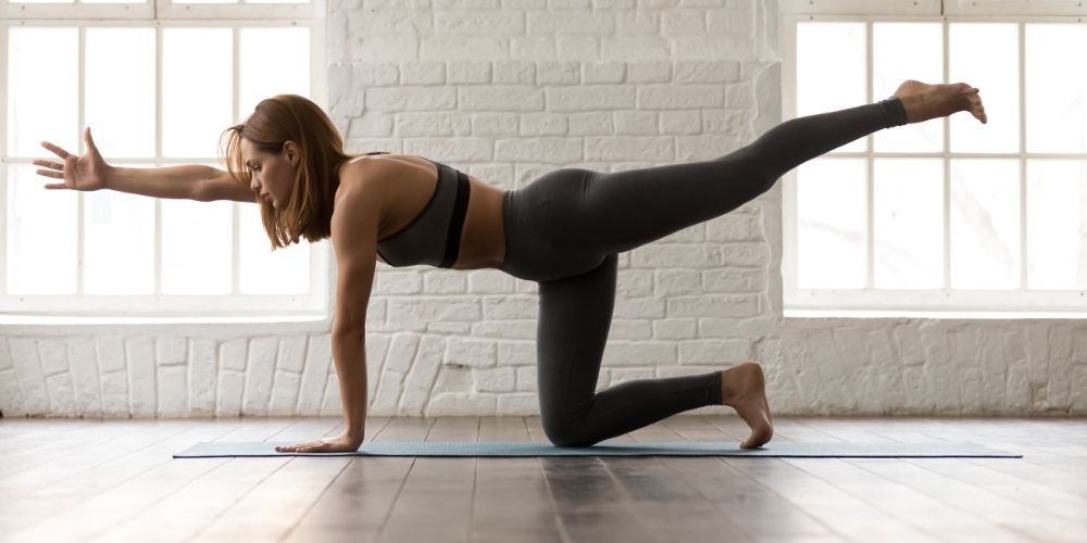 Woman in sports bra and leggings doing bird dogs on a yoga mat.