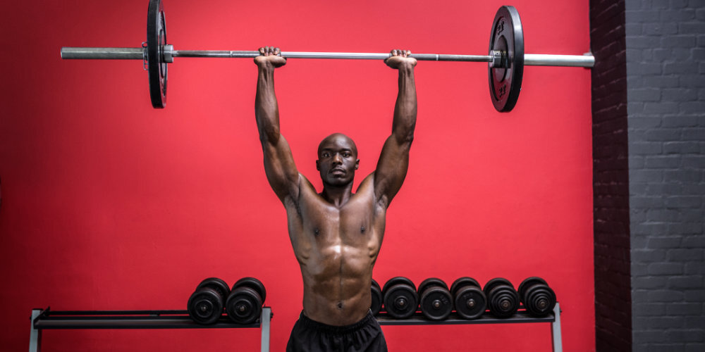 Shirtless muscular man holding barbell overhead.