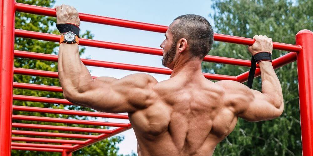 athletic man doing pull ups outside