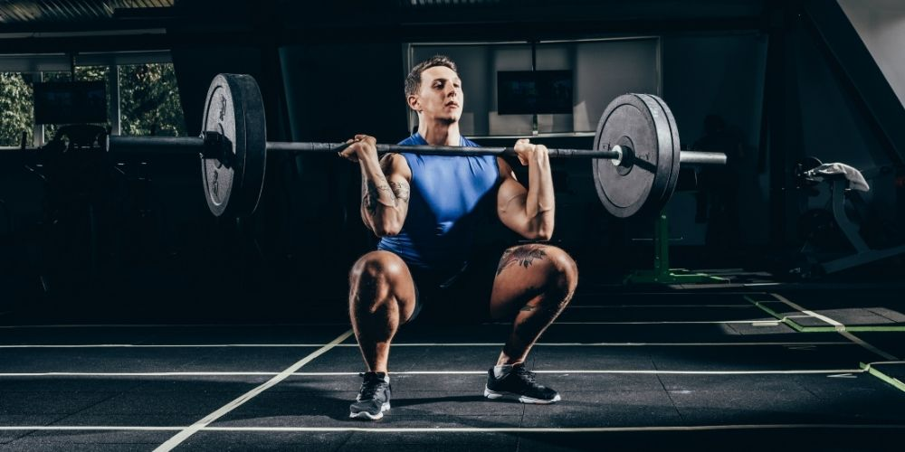 Man in blue shirt and black shorts in the bottom position of a front squat.