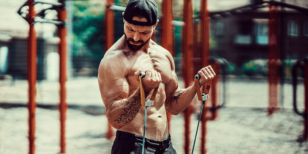 Fit muscular man working out with bands outside