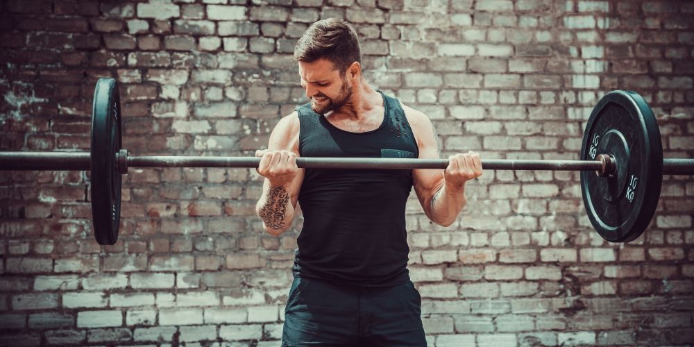 muscular man doing barbell bicep curl