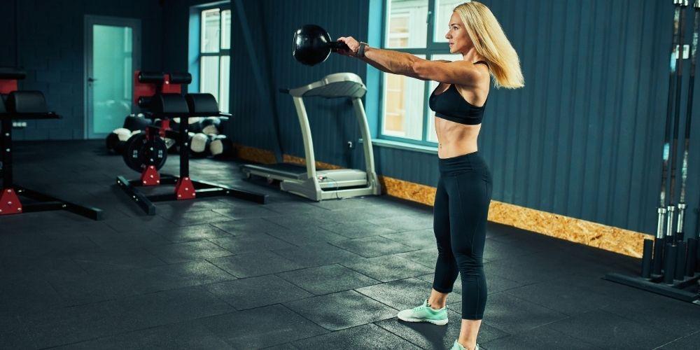 Blonde woman wearing leggings and sports bra doing kettlebell swings inside a gym.