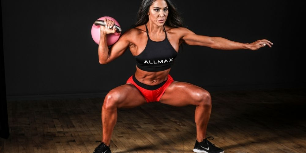 Woman in red shorts and black sports bra doing sumo squats.