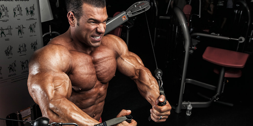 Allmax athlete performing cable fly
