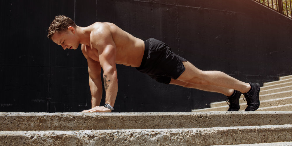 Muscular shirtless man in black shorts and shoes doing pushups outside.