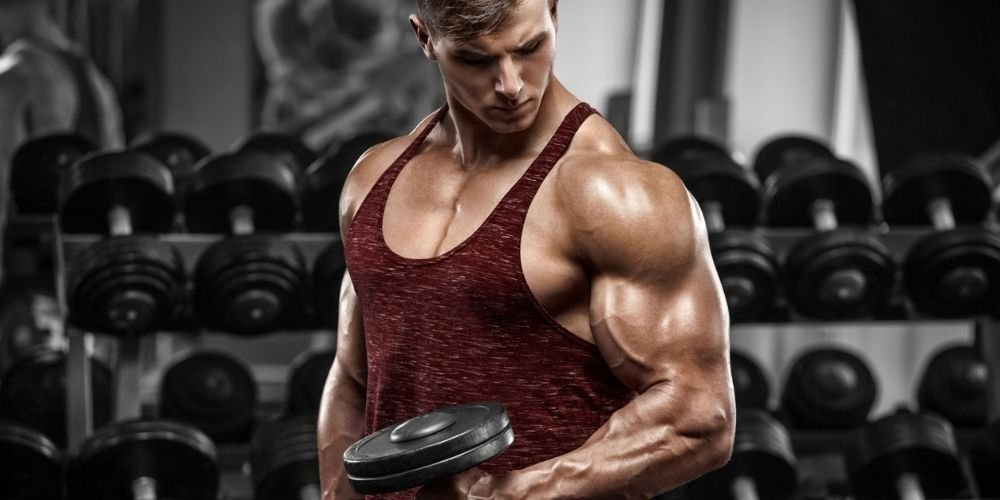 Muscular man in red tank doing single arm hammer curls at gym.