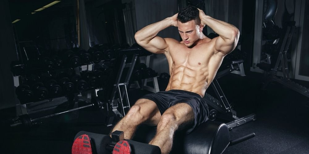 Ripped man doing crunches in the gym