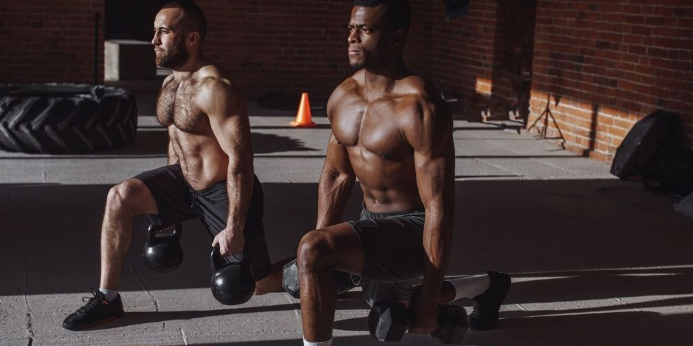 Men doing lunges with kettlebells and dumbbells.