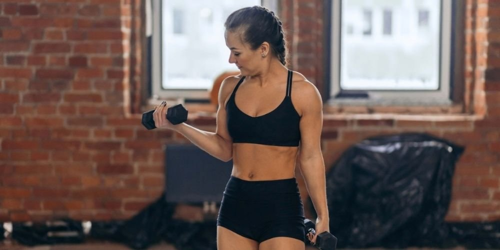 Woman in black sports bra and shorts holding a black dumbbell performing a bicep curl.
