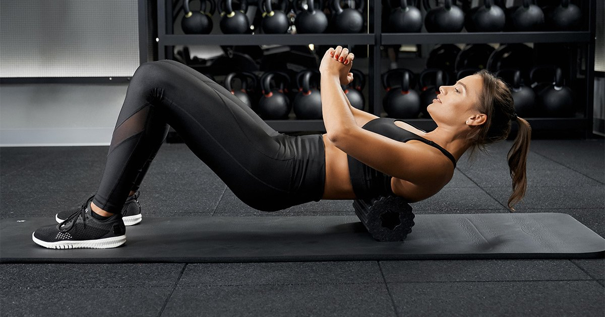 Fit female foam rolling on the floor in the gym