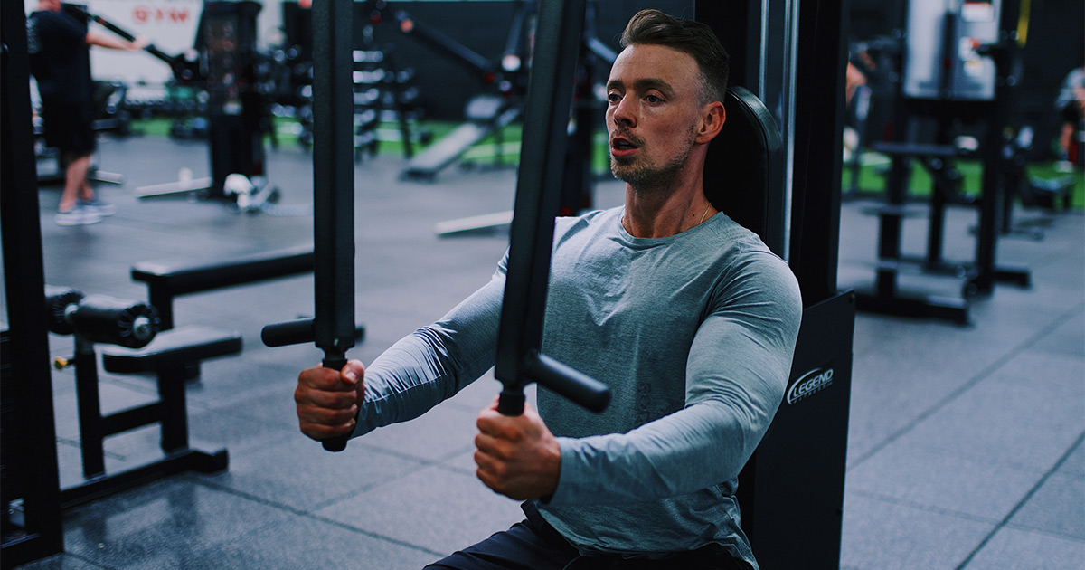 Muscular man doing machine chest flys in the gym