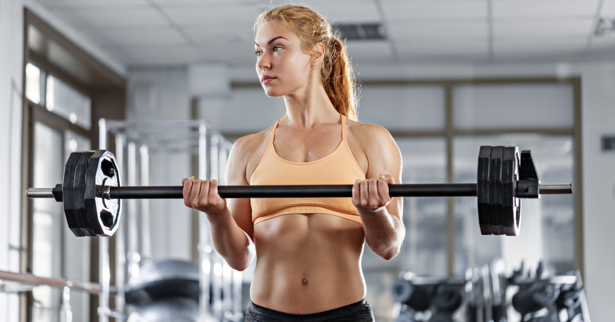 Fit woman doing barbell bicep curls in gym.
