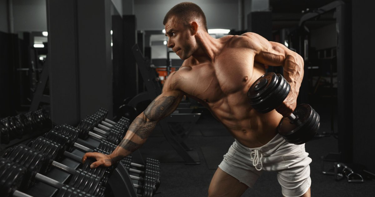 Muscular man doing dumbbell rows in the gym
