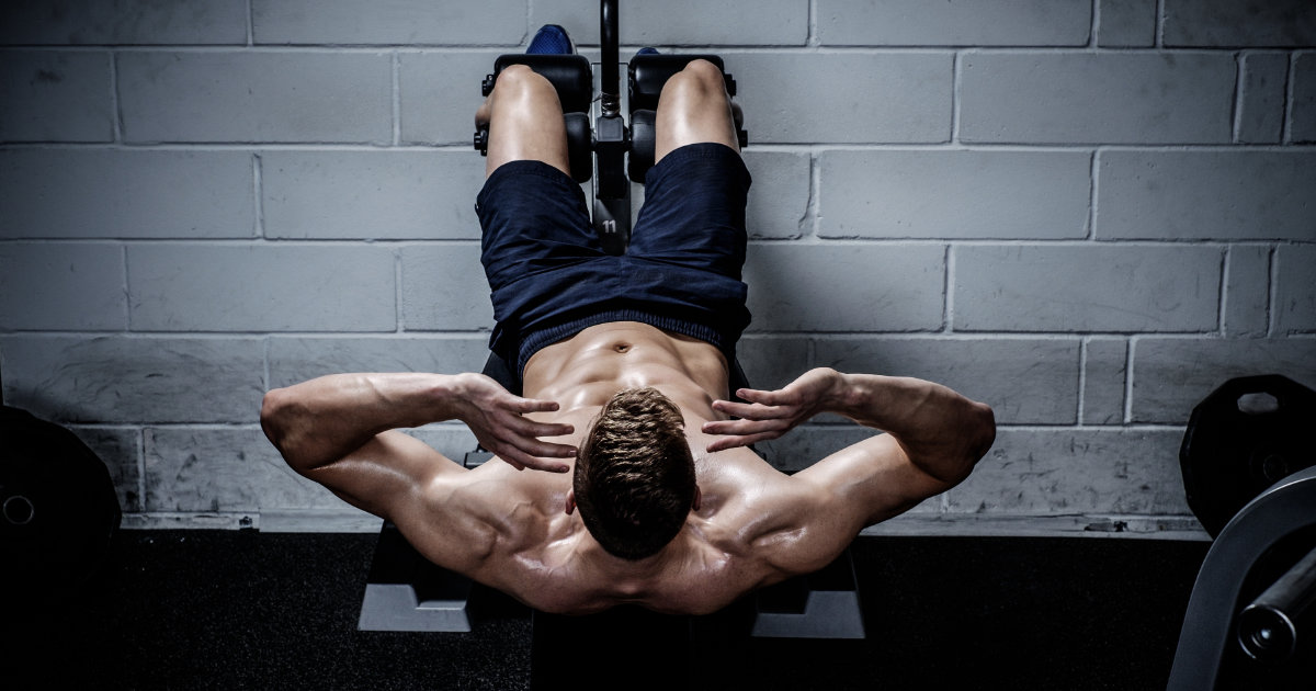 Man doing GHD sit ups in gym.