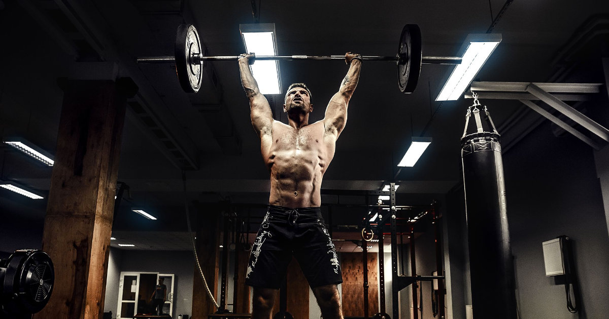 Man in gym performing overhead barbell press