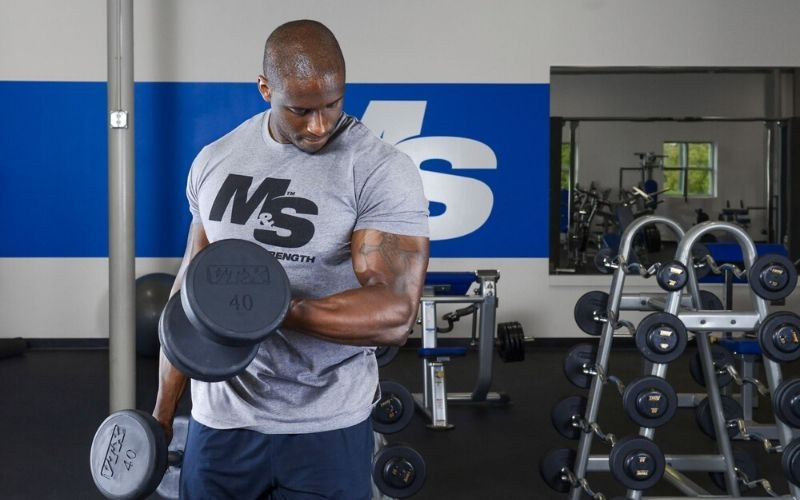 Muscle & Strength Athlete Doing Bicep Curls in Gym