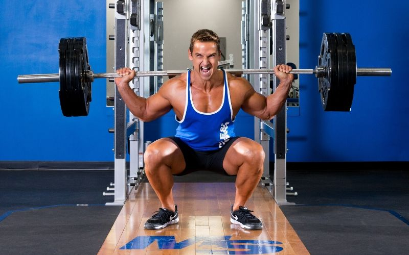 Muscle & Strength Athlete Barbell Squatting in Gym