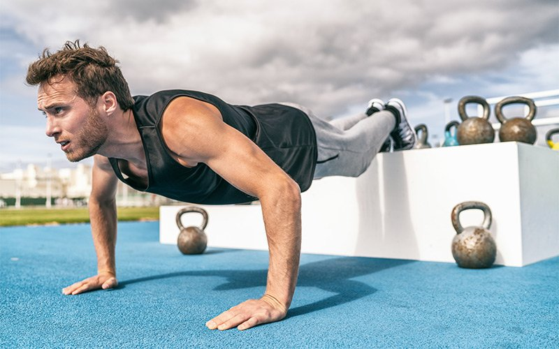 Man in black tank top doing feet elevated pushup