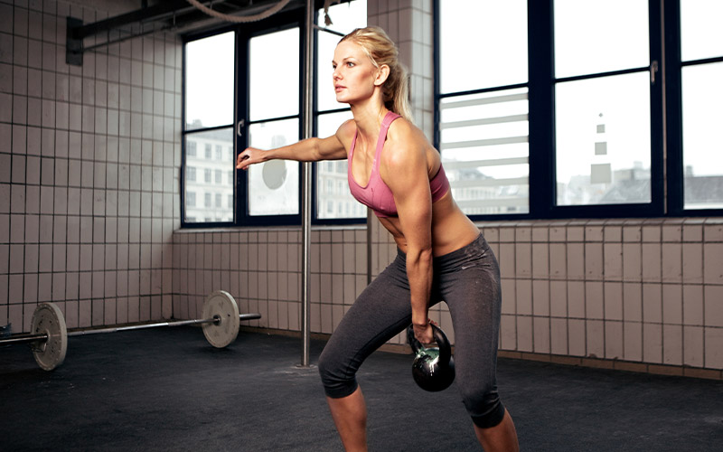 Athletic woman doing kettlebell swings