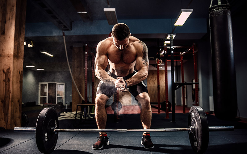 Man in black shorts prepping to perform barbell deadlift