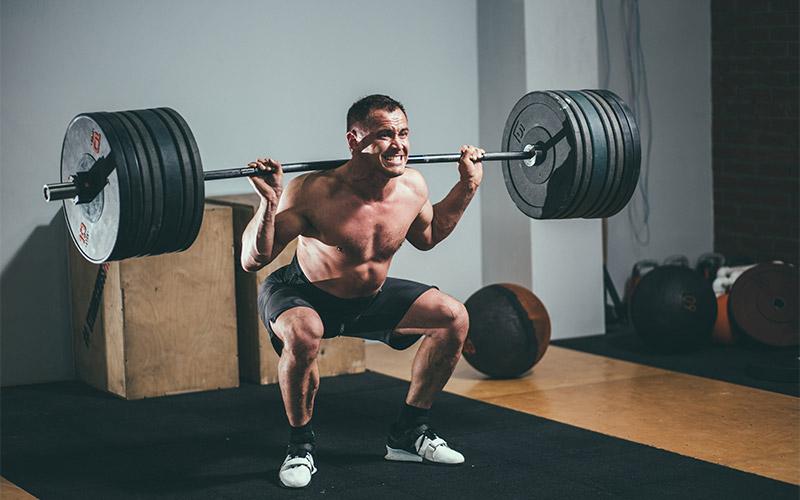 Man in black shorts squatting heavy in gym