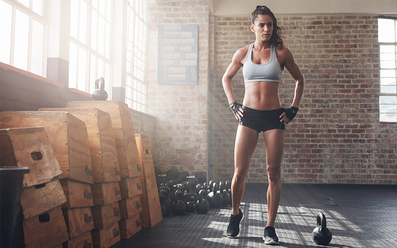 Female athlete with multiple kettlebells and plyo boxes