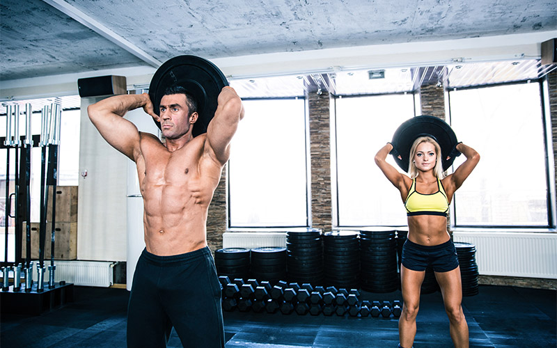 Man and woman performing overhead plate tricep extensions