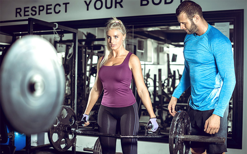 Girl in purple tank top performing trap-bar deadlift with coach in blue shirt
