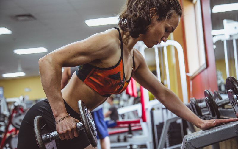 Athletic woman in red sports bra performing a single arm dumbbell row off of a dumbbell rack.